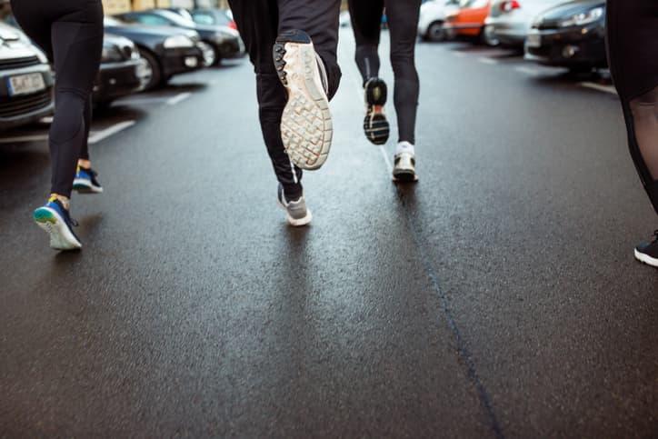Vier Läufer joggen auf der Straße